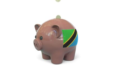 Putting money into piggy bank with flag of Tanzania. Tax system system or savings related conceptual 3D rendering 写真素材