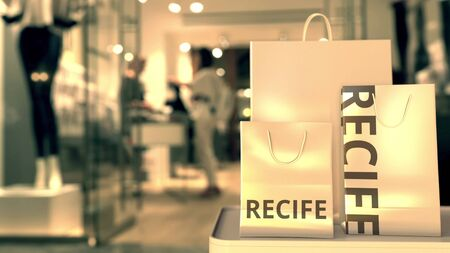 Paper shopping bags with Recife caption against blurred store entrance. Retail in Brazil related conceptual 3D rendering Imagens
