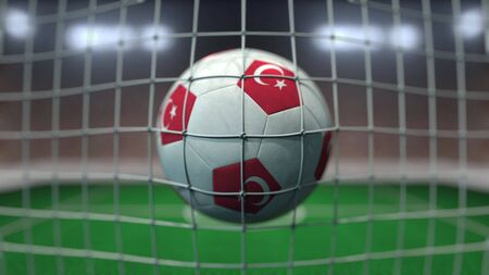 Football with flags of Turkey in net against blurred stadium. Conceptual 3D rendering