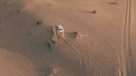 Aerial shot of an unknown white SUV driving fast along sand dunes in the desert, UAE