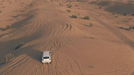 DUBAI, UNITED ARAB EMIRATES - JANUARY 4, 2020. Aerial tracking shot of a Toyota Sequoia full-sized SUV driving along sand dunes in the desert