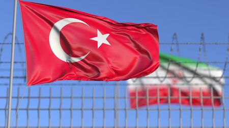 Waving flags of Turkey and Iran separated by barbed wire fence.Conflict related conceptual 3D rendering