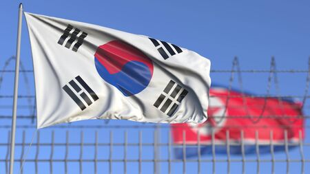 Waving flags of South Korea and North Korea separated by barbed wire fence. Conflict related conceptual 3D rendering Stock Photo