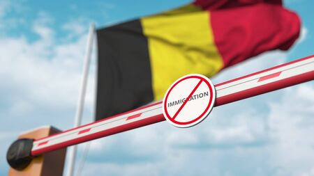 Barrier gate with no immigration sign being closed with flag of Belgium as a background. Belgian Border closure or immigration ban. 3D rendering Foto de archivo