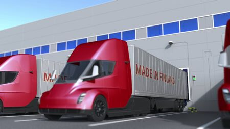 Modern semi-trailer trucks with MADE IN FINLAND text being loaded or unloaded at warehouse. Finnish business related 3D rendering