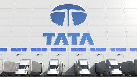 Electric semi-trailer trucks at warehouse loading bay with TATA logo on the wall. Editorial 3D rendering