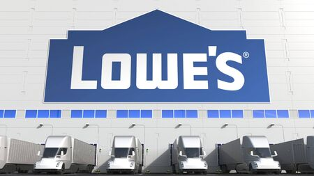 Electric semi-trailer trucks at warehouse loading bay with LOWES logo on the wall. Editorial 3D rendering