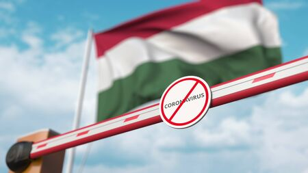 Closed boom gate with STOP CORONAVIRUS sign on the Hungarian flag background. Quarantine in Hungary. 3D rendering Imagens