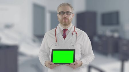 Concerned doctor holds modern tablet PC with green screen