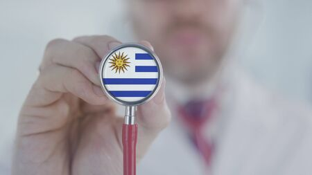 Doctor holds stethoscope bell with the Uruguayan flag. Healthcare in Uruguay