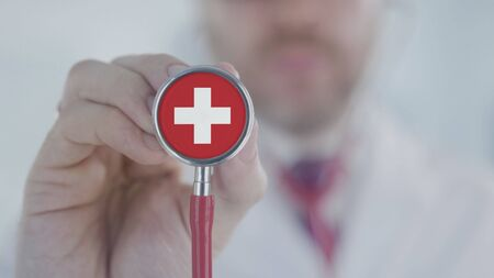 Medical doctor holds stethoscope bell with the Swiss flag. Healthcare in Switzerland