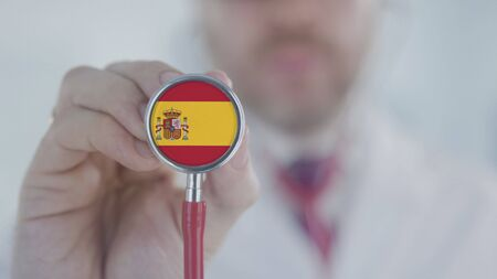 Doctor holds stethoscope bell with the flag. Healthcare related shot Stock Photo