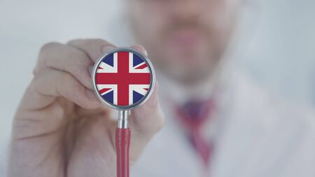 Doctor listening with the stethoscope with flag of the UK. British healthcare Stock Photo