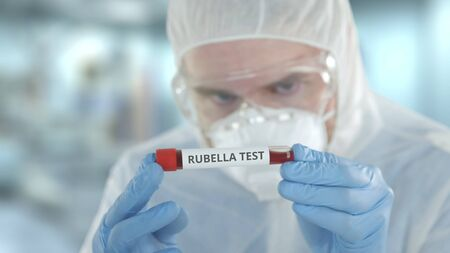 Unknown laboratory assistant wearing protection suit examines vial with rubella test