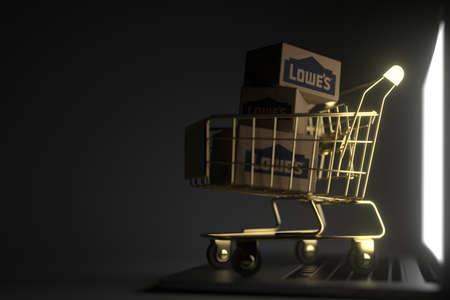 Cartons with LOWES logo in golden shopping trolley on the laptop. Editorial premium service related 3D rendering Editorial