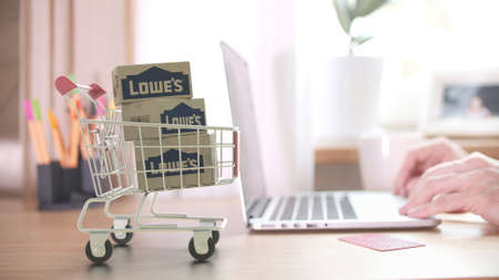 Cartons with LOWES logo in shopping trolley near customer with laptop. Editorial online shopping from home 3D rendering Editorial