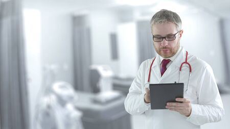 Doctor works on tablet PC in a hospital ward Imagens