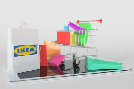 Shopping cart on a tablet computer and paper bag with Ikea logo. Editorial e-commerce related 3D rendering