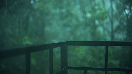 Heavy rain, raindrops hit balcony railing