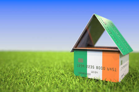 Flag of the Republic of Ireland on plastic bank card house in the grass. Mortgage related 3D rendering