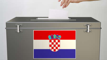 Putting paper ballot into ballot box with flag Stock Photo