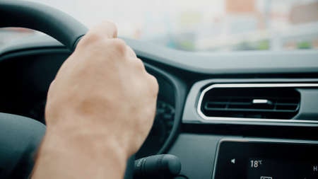 Driving a car, mans hand on the steering wheel close-up shot