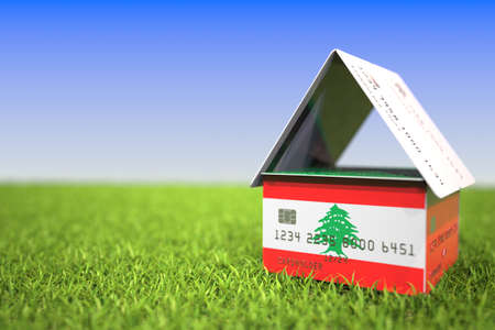 Flag of Lebanon on bank card house in the grass. Mortgage related 3D rendering