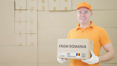Warehouse worker holds cardboard box with printed FROM ROMANIA text on it
