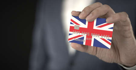Businessman holding plastic bank card with printed flag of the United Kingdom, fictional numbers