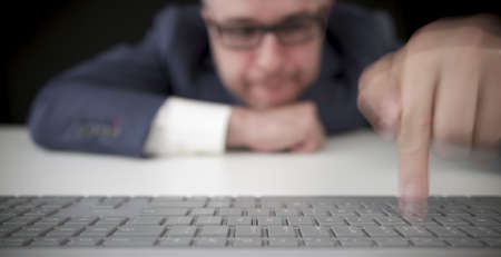 Funny inexperienced businessman types with one finger on the computer keyboard Stock Photo