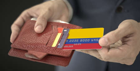 Man pulls plastic bank card with flag of Colombia out of his wallet, fictional card number