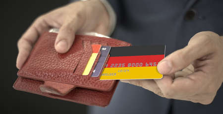 Man pulls plastic bank card with flag of Gemany out of his wallet, fictional card number Stock Photo