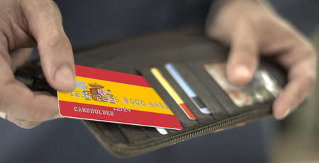 Pulling plastic bank card with flag of Spain out of the wallet, fictional card number