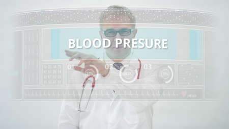 BLOOD PRESURE tab is scrolled by a doctor on a modern display 免版税图像