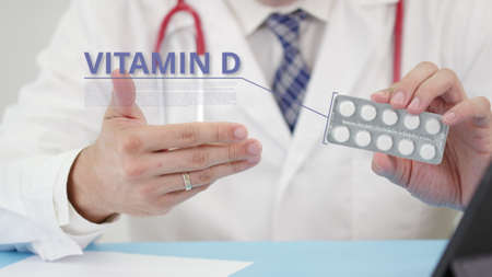 Vitamin d blister pack with tablets in doctors hand