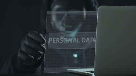 Unknown hacker wearing black mask pulls PERSONAL DATA tab from a laptop. Hacking concept Stock Photo