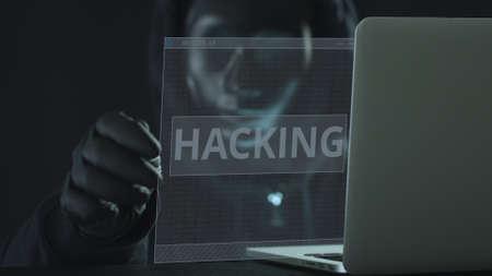 Hacker wearing black mask pulls HACKING tab from a laptop Stock Photo