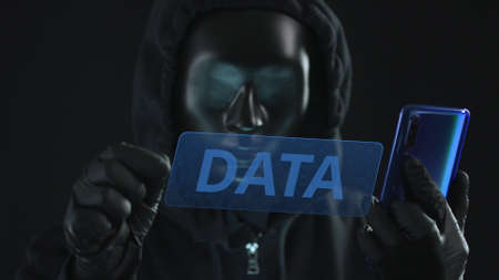 Hacker wearing black mask pulls DATA tab from a smartphone. Hacking concept