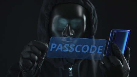 Hacker wearing black mask pulls PASSCODE tab from a smartphone. Hacking concept Stock Photo