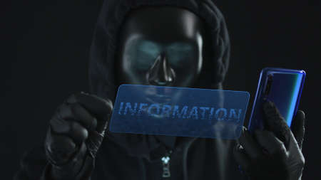 Hacker wearing black mask pulls INFORMATION tab from a smartphone. Hacking concept