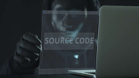 Hacker wearing black mask pulls SOURCE CODE tab from a laptop. Hacking concept Stock Photo