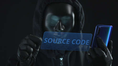 Hacker wearing black mask pulls SOURCE CODE tab from a smartphone. Hacking concept Stock Photo