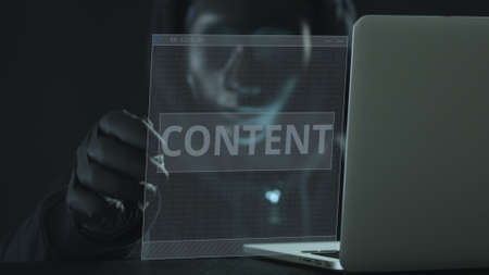 A hacker wearing black mask pulls CONTENT tab from a laptop. Hacking concept