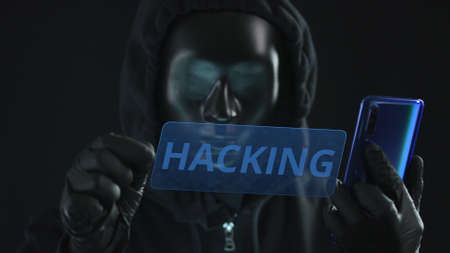 Hacker wearing black mask pulls HACKING tab from a smartphone Stock Photo
