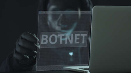 A hacker wearing black pulls BOTNET tab from a laptop. Hacking concept Stock Photo