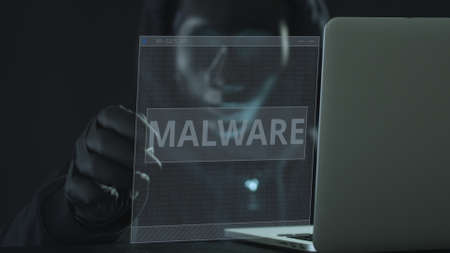 Unknown hacker wearing black mask pulls MALWARE tab from a laptop. Hacking concept Stock Photo