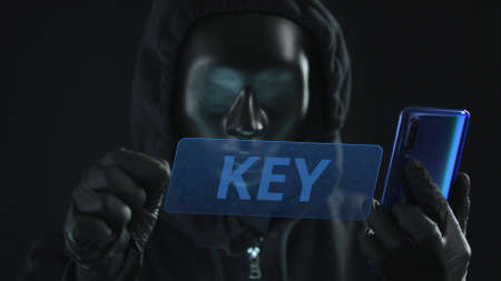 Hacker wearing black mask pulls KEY tab from a smartphone. Hacking concept Stock Photo