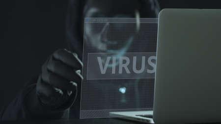 Hacker wearing black mask pulls VIRUS tab from a laptop. Hacking concept