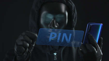 Hacker wearing black mask pulls PIN tab from a smartphone. Hacking concept