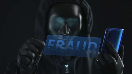 Hacker wearing black mask pulls FRAUD tab from a smartphone